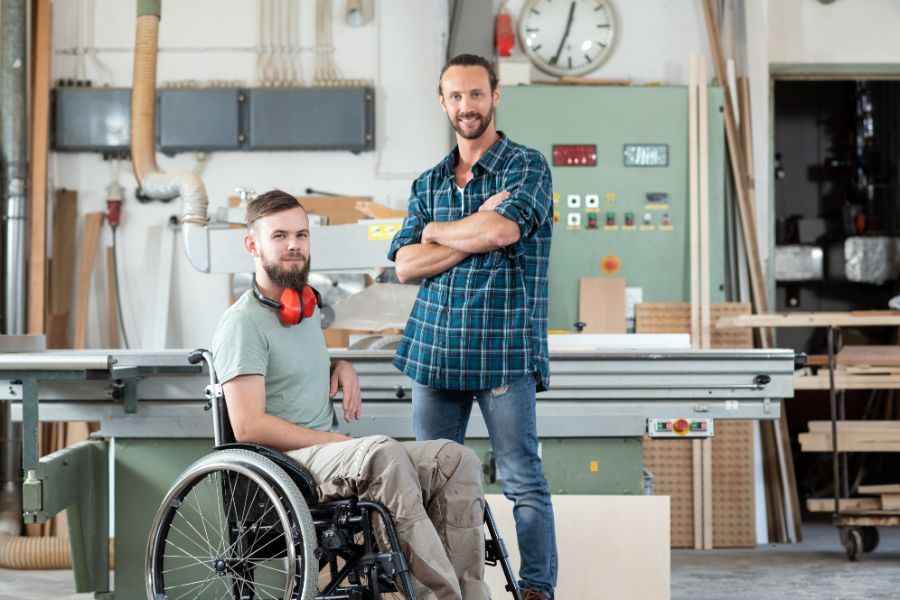 Carpenter In Wheelchair In Workshop With Colleague